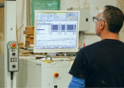 Operario manejando control numérico para la confección de piezas de mobiliario.