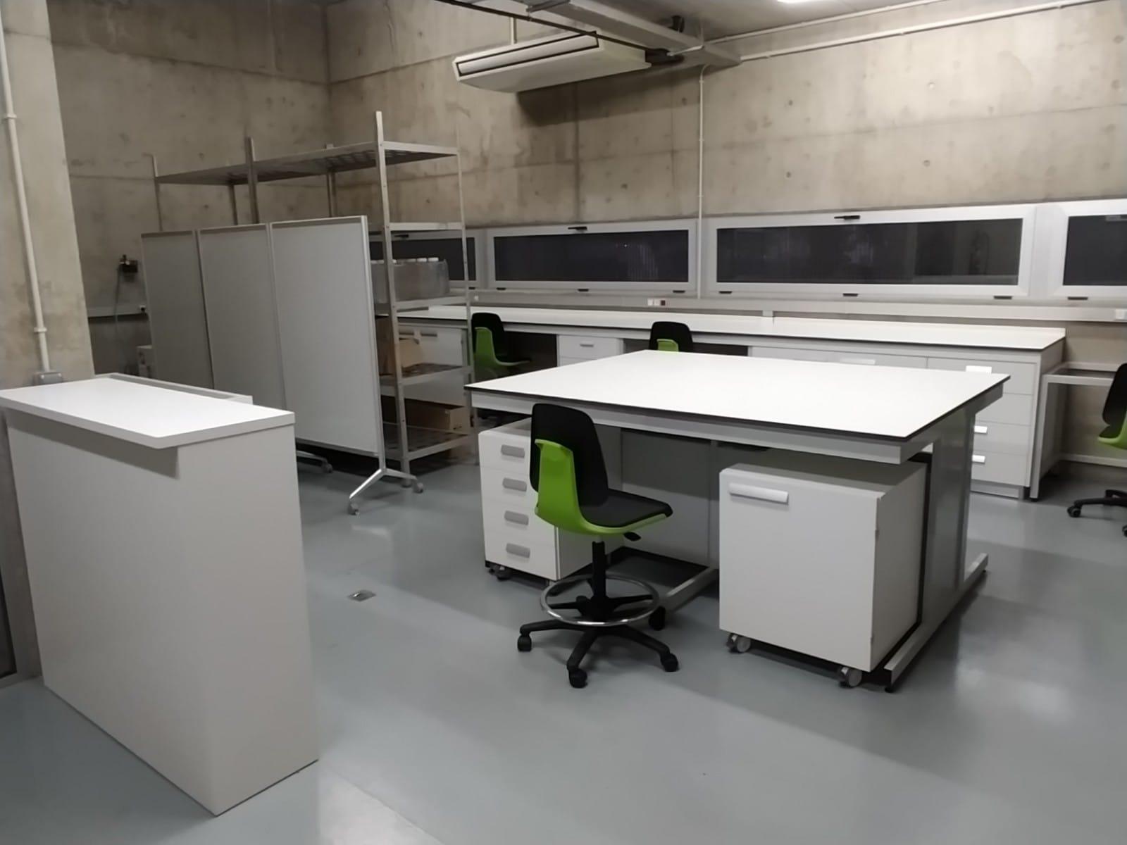 Vista de laboratorio que incluye módulo fregadero, isla, muebles y poyatas de laboratorio, así como taburetes Bimos Labsit de laboratorio.