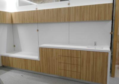 Vista frontal de bancada clínica con encimera de krion blanco, vitrinas suspendidas y frentes con acabado madera.